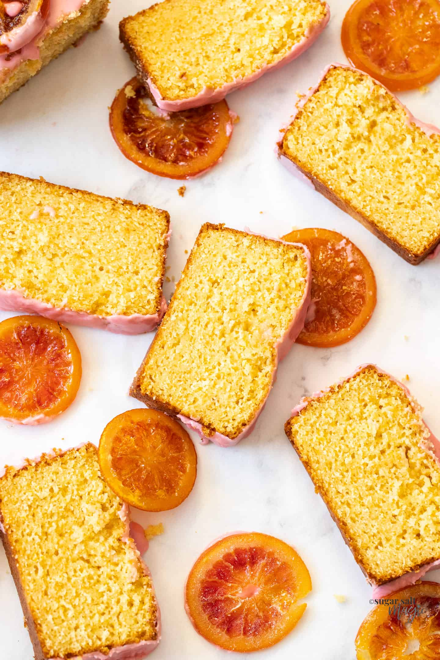 Slices of orange loaf cake surrounded by candied oranges.