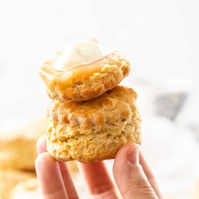 Two scones being held up by a hand.