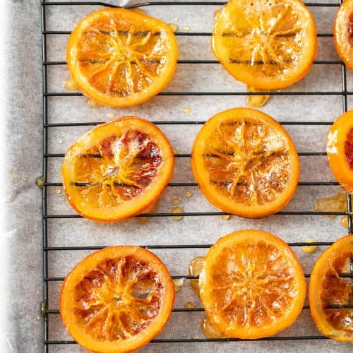 Top down view of 6 candied orange slices on a wire rack.