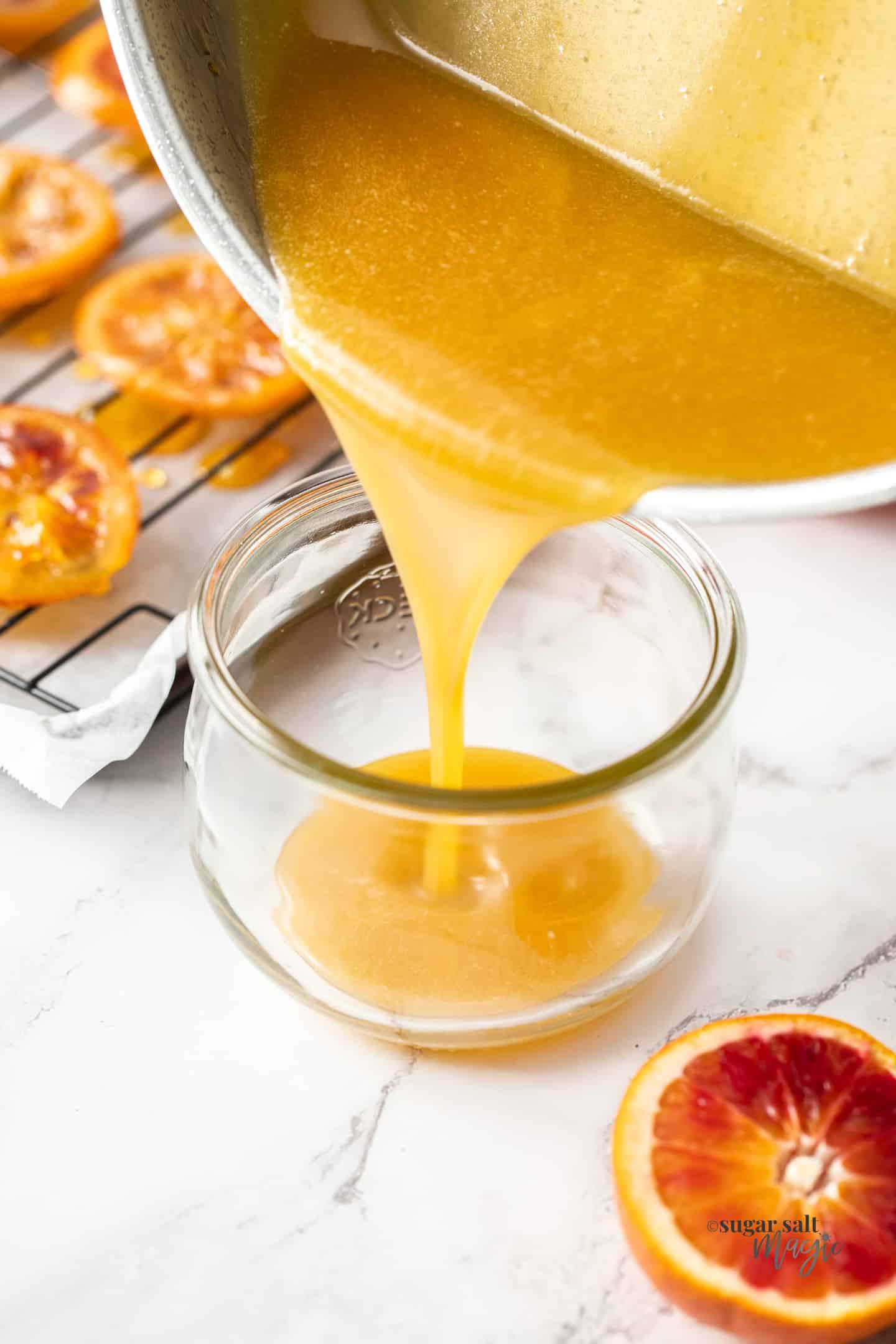 Orange caramel sauce being poured into a glass jar.