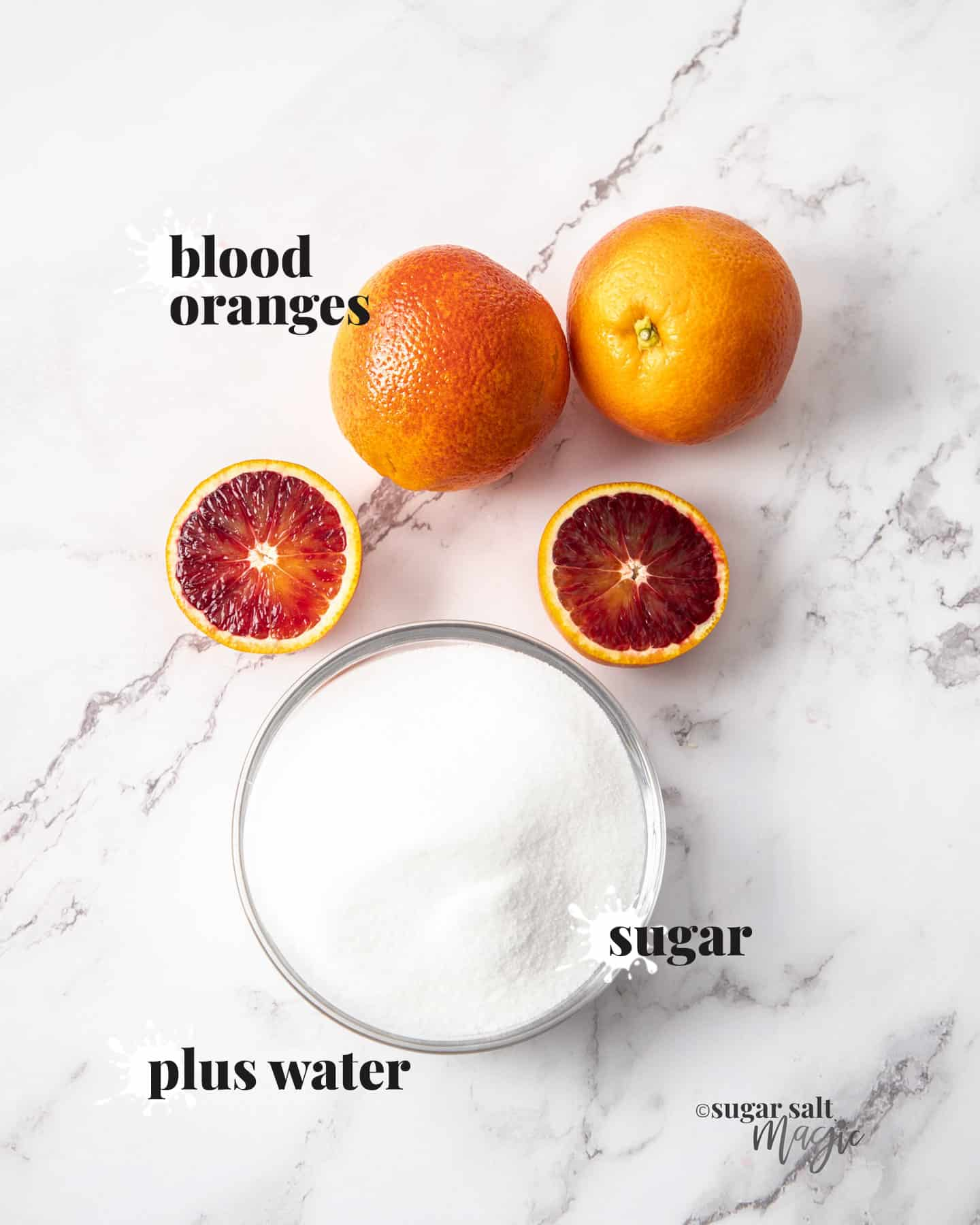 Blood oranges and sugar on a marble background.
