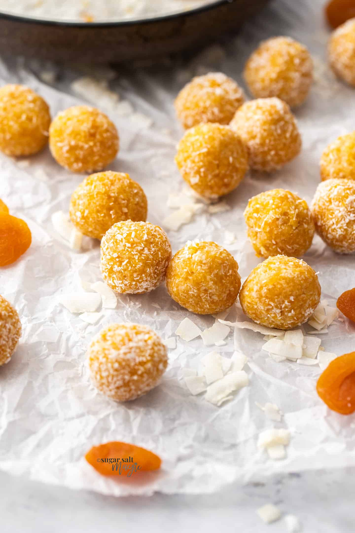 A batch of apricot bliss balls on a sheet of baking paper.