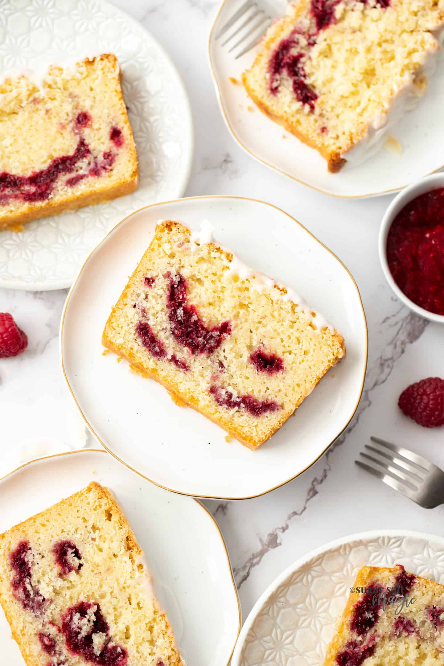 Top down view of 5 slices of cake on white plates with raspberry compote next to it..