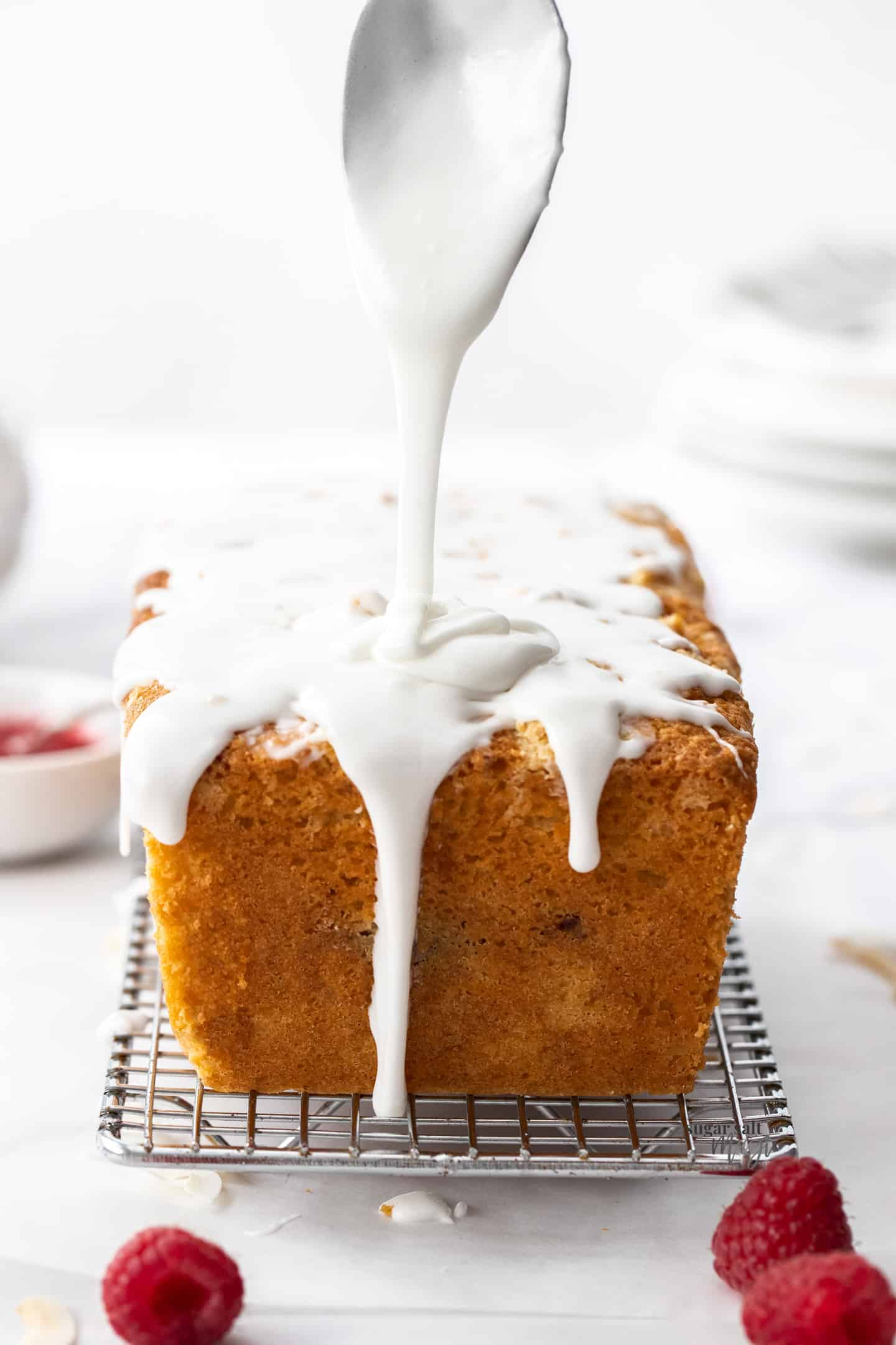 A spoon drizzling white icing directly down onto a coconut loaf cake.