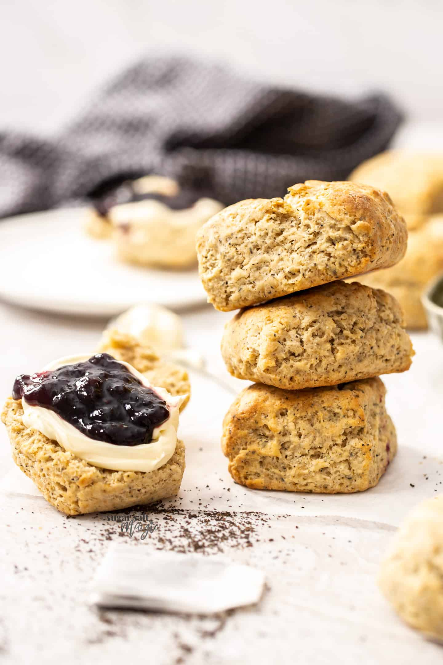 3 stacked scones with half a scone next to them, topped with cream and jam.