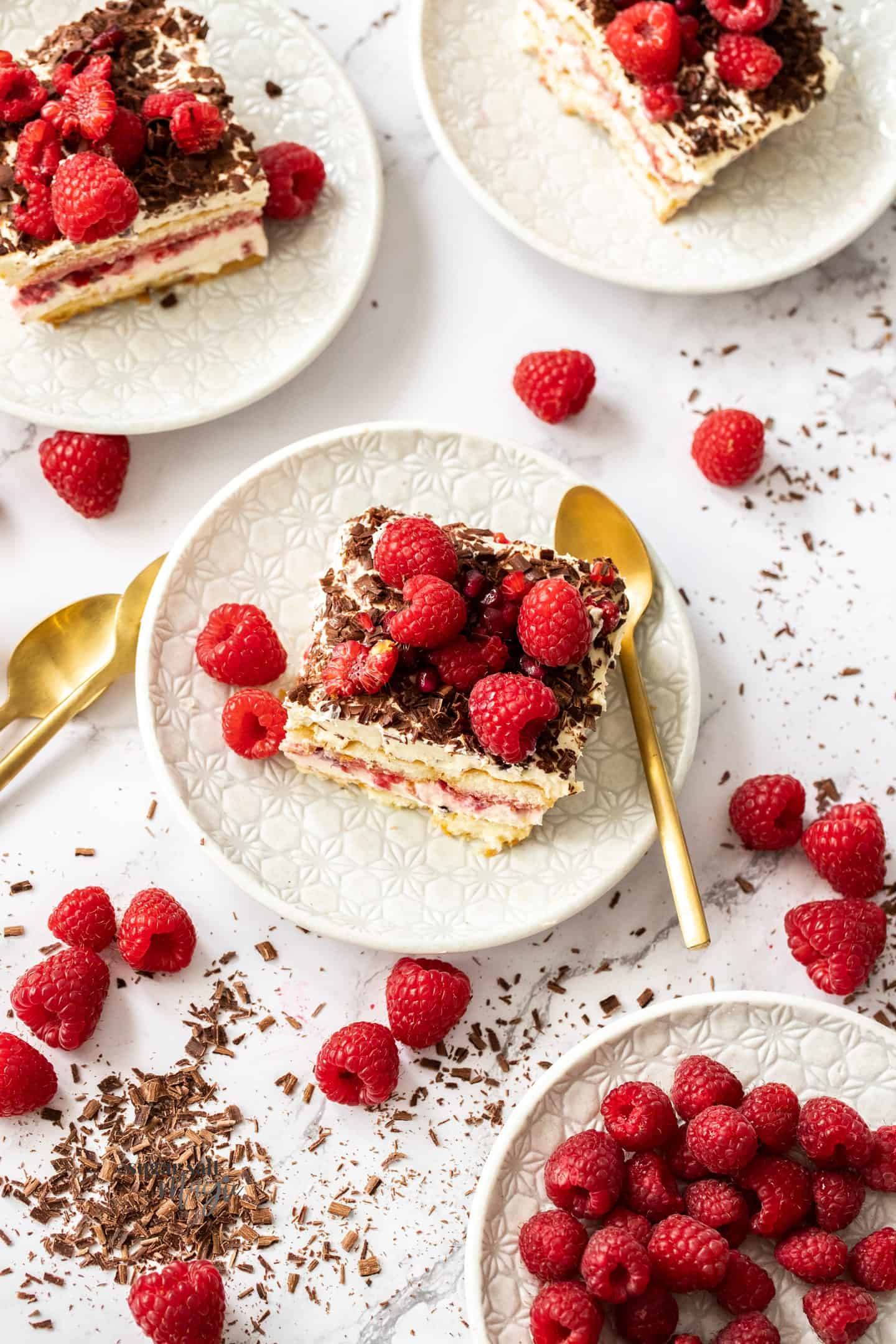 Top down view of 4 small plates of raspberry tiramisu surrounded by raspberries.
