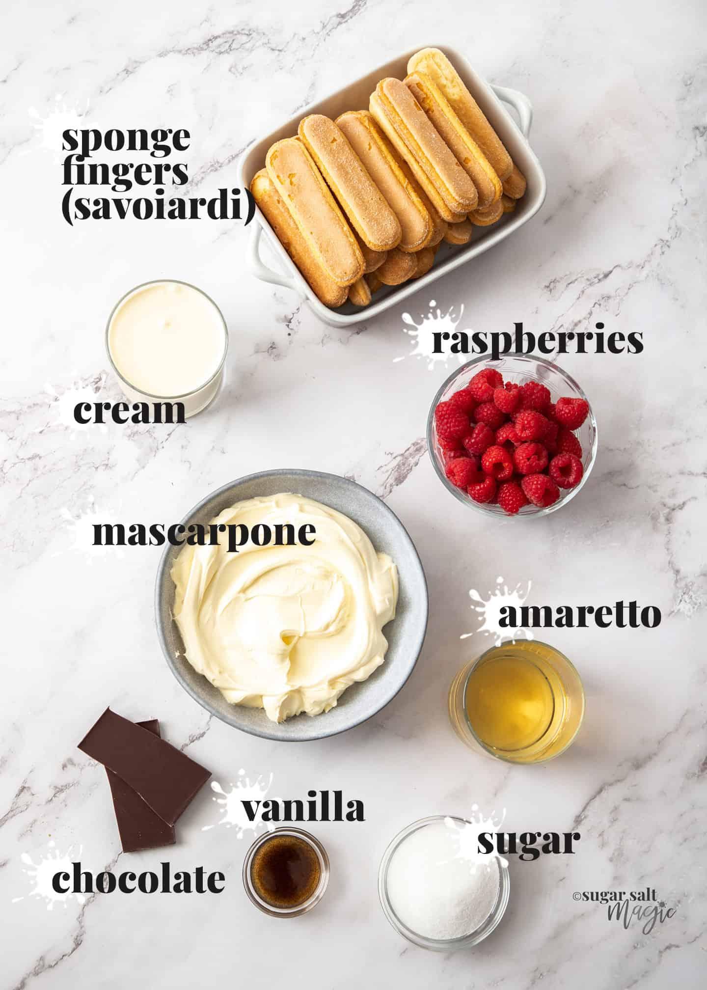 Ingredients for raspberry tiramisu on a marble background.