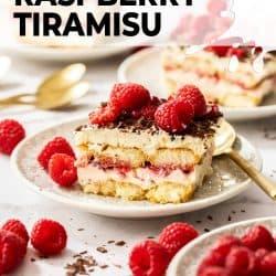 A slice of raspberry tiramisu on a white plate surrounded by fresh raspberries.