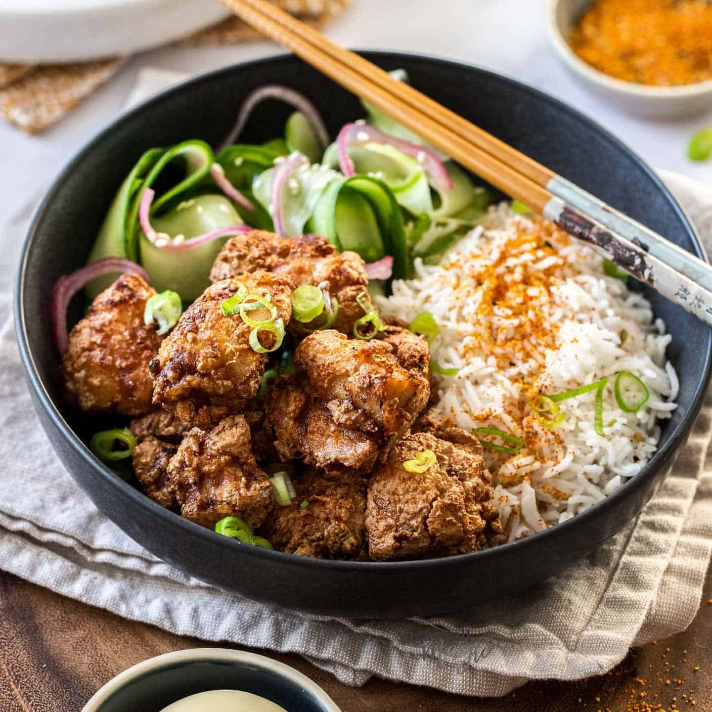 A black bowl filled with salad, rice and fried chicken, on a wooden platter.