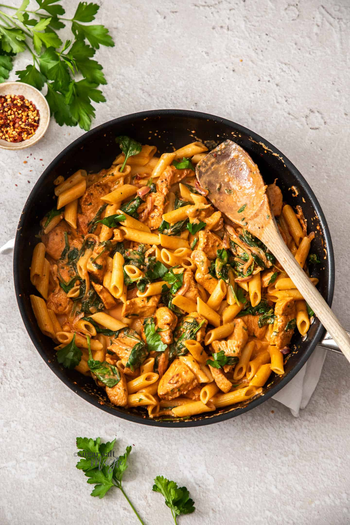 Top down view of pasta and chicken in a skillet with a wooden spoon.