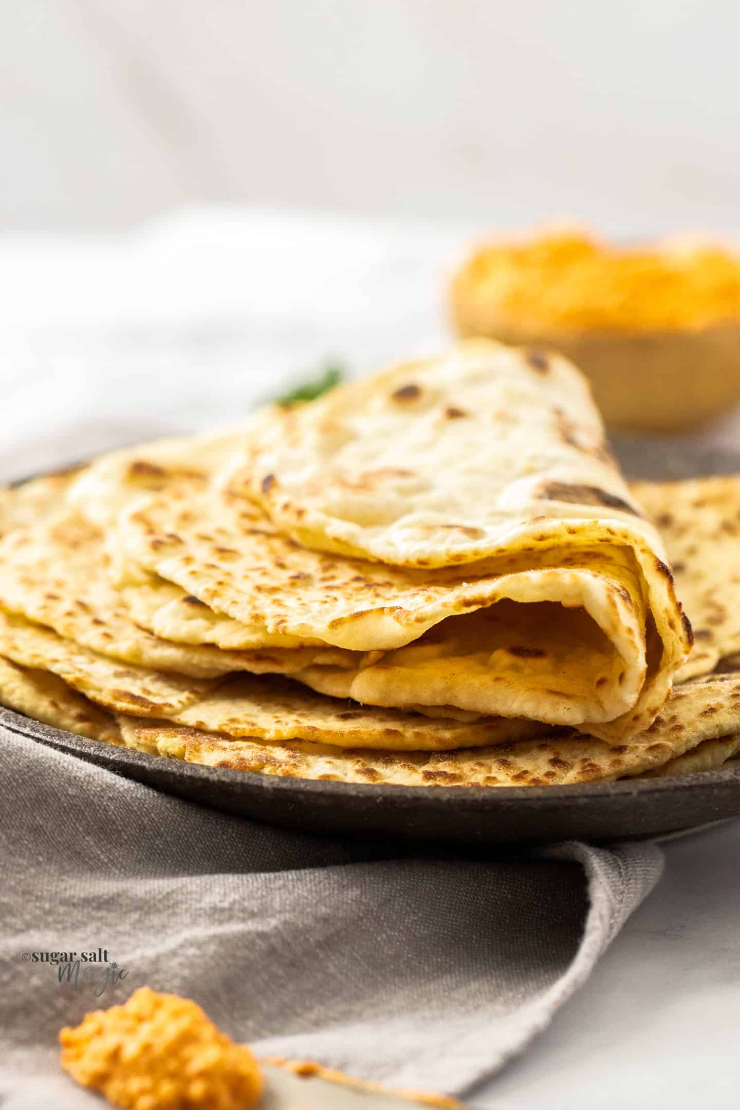 Some flatbreads folded on a brown plate.