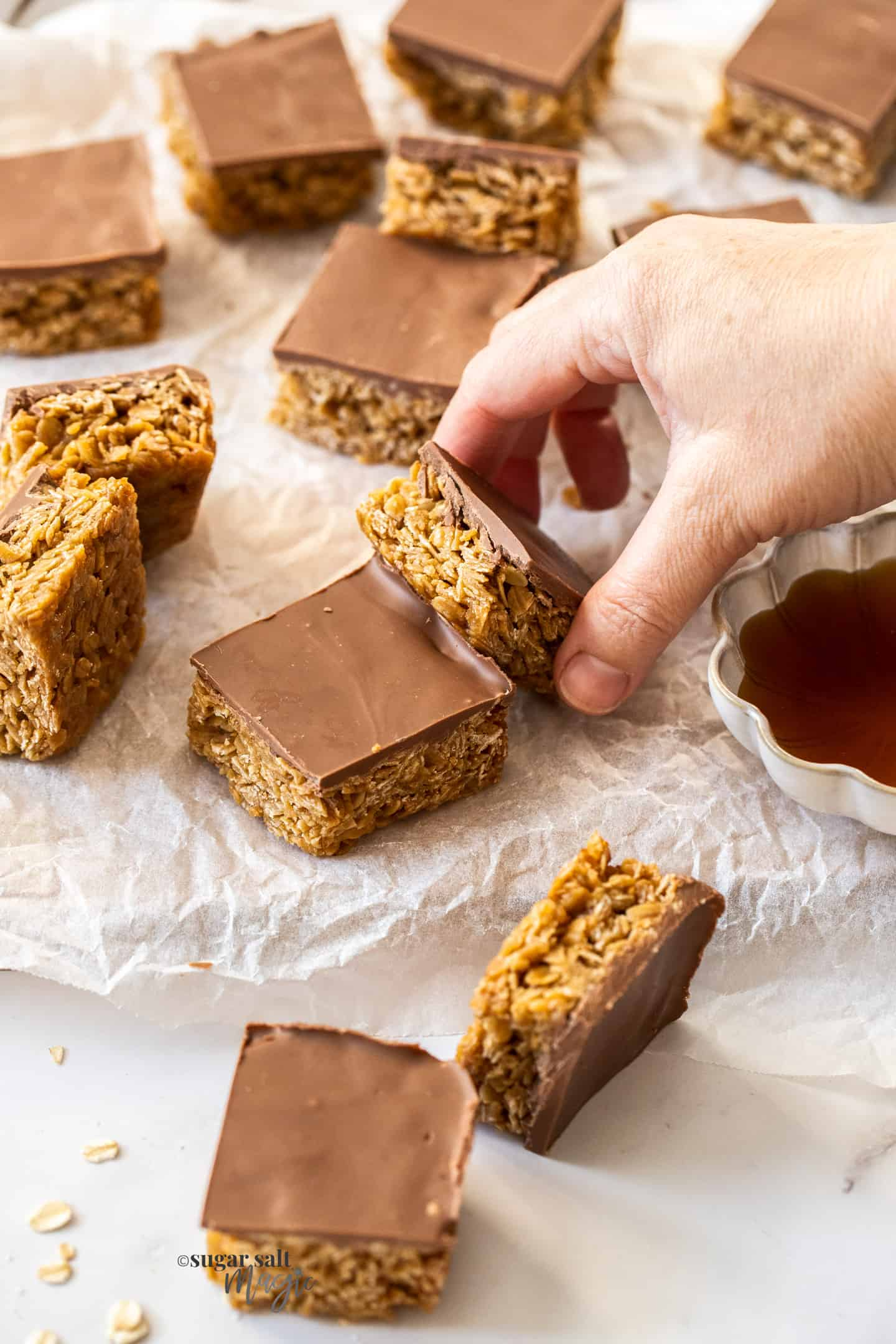 A hand grabbing a chocolate flapjack from a batch.