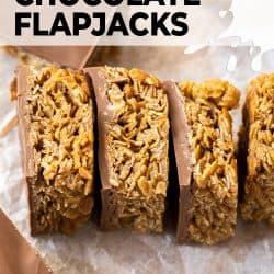 A row of chocolate flapjacks lined up on a sheet of baking paper.