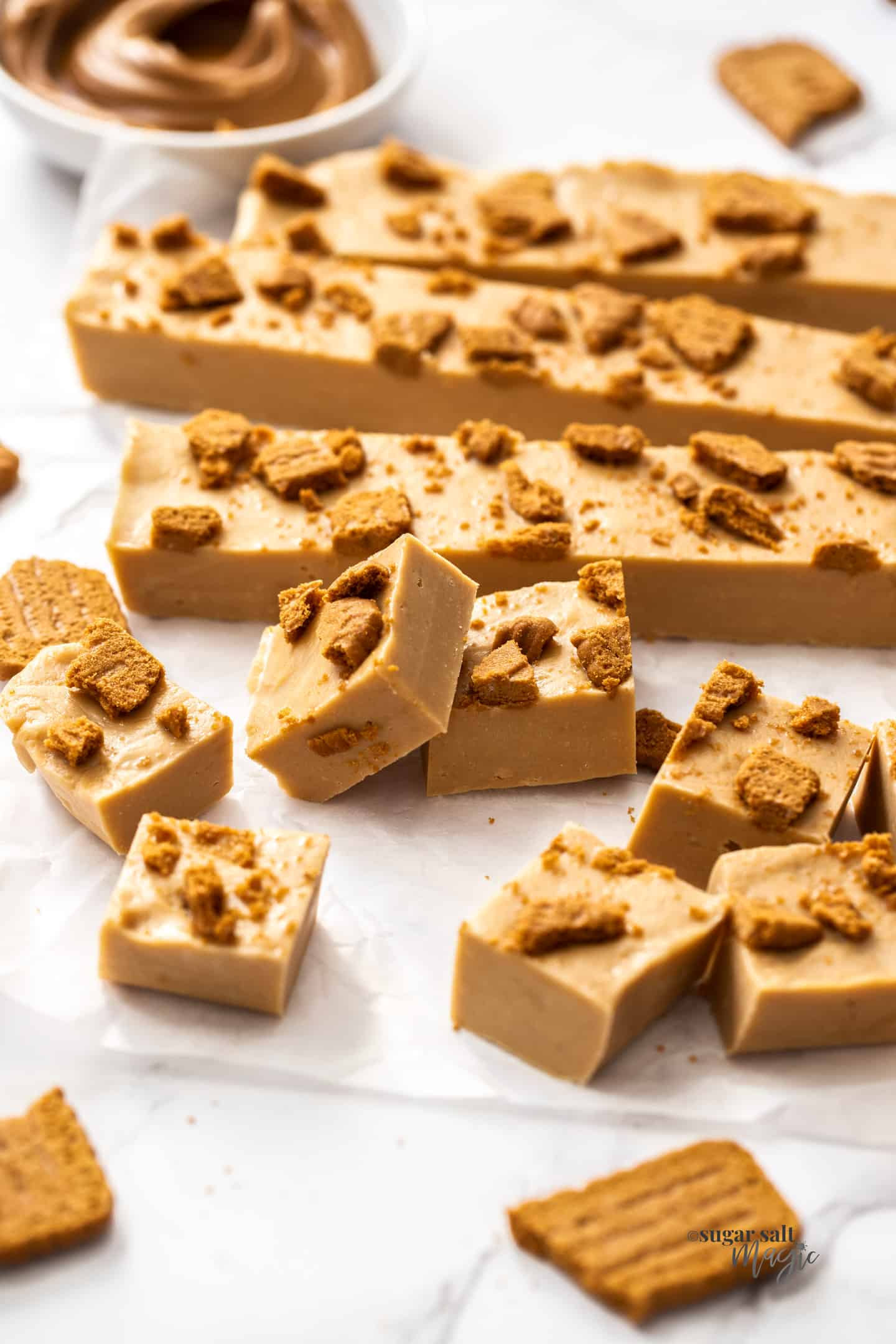 A batch of biscoff fudge, some cut into squares, some in sticks.