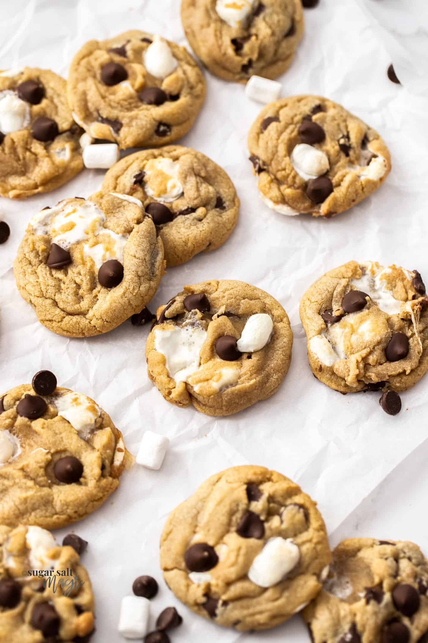 A batch of chocolate chip marshmallow cookies on a sheet of baking paper.