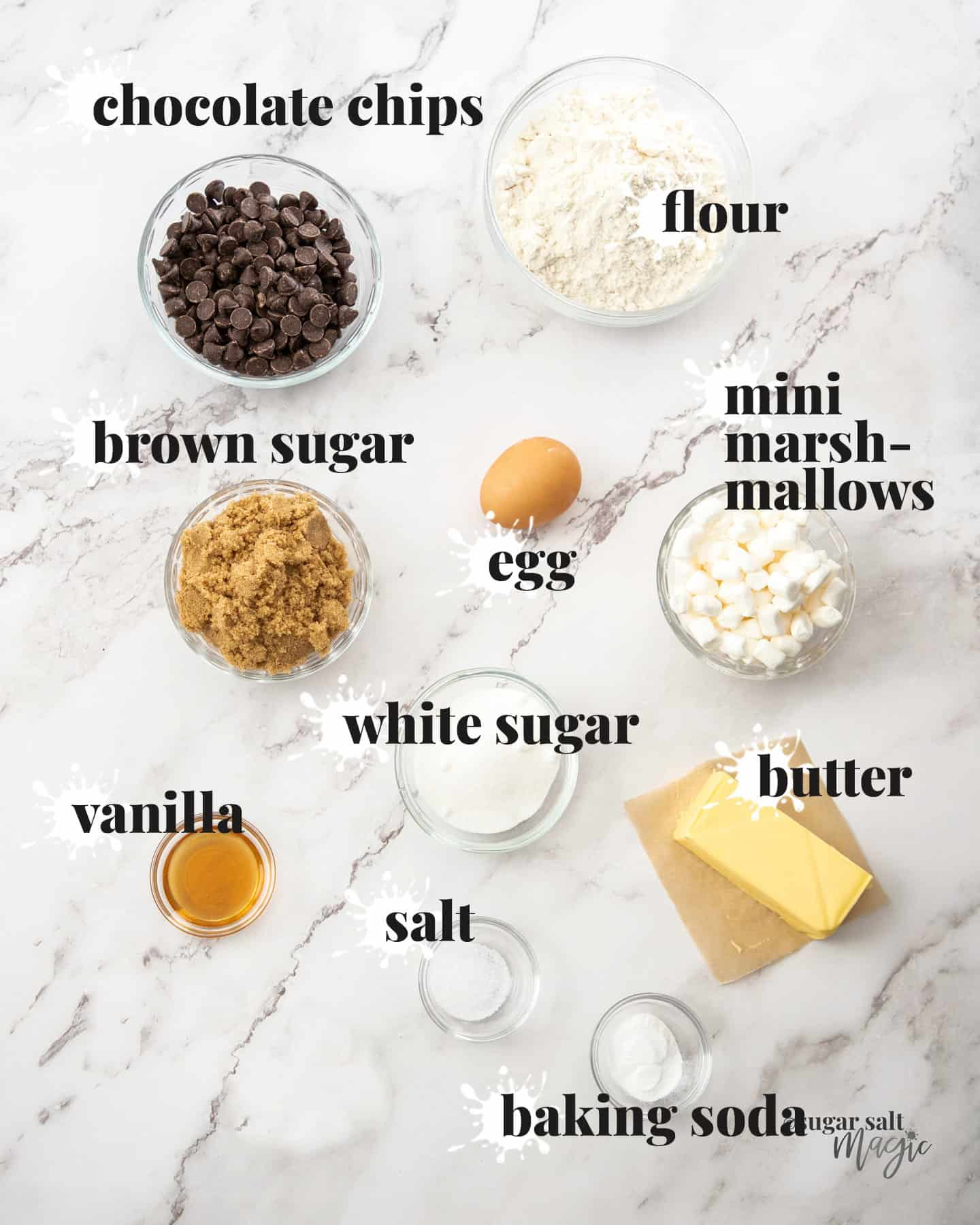Ingredients for marshmallow chocolate chip cookies on a marble surface.