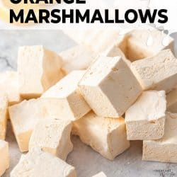 A pile of orange marshmallows on a grey marble surface.