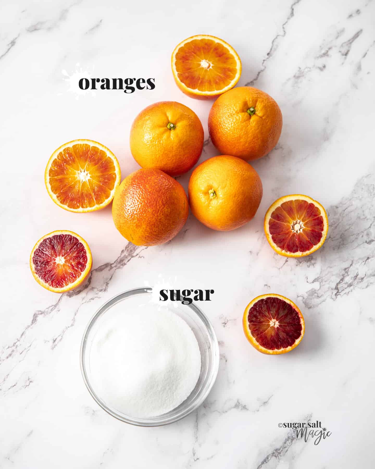 Oranges and sugar on a marble benchtop.