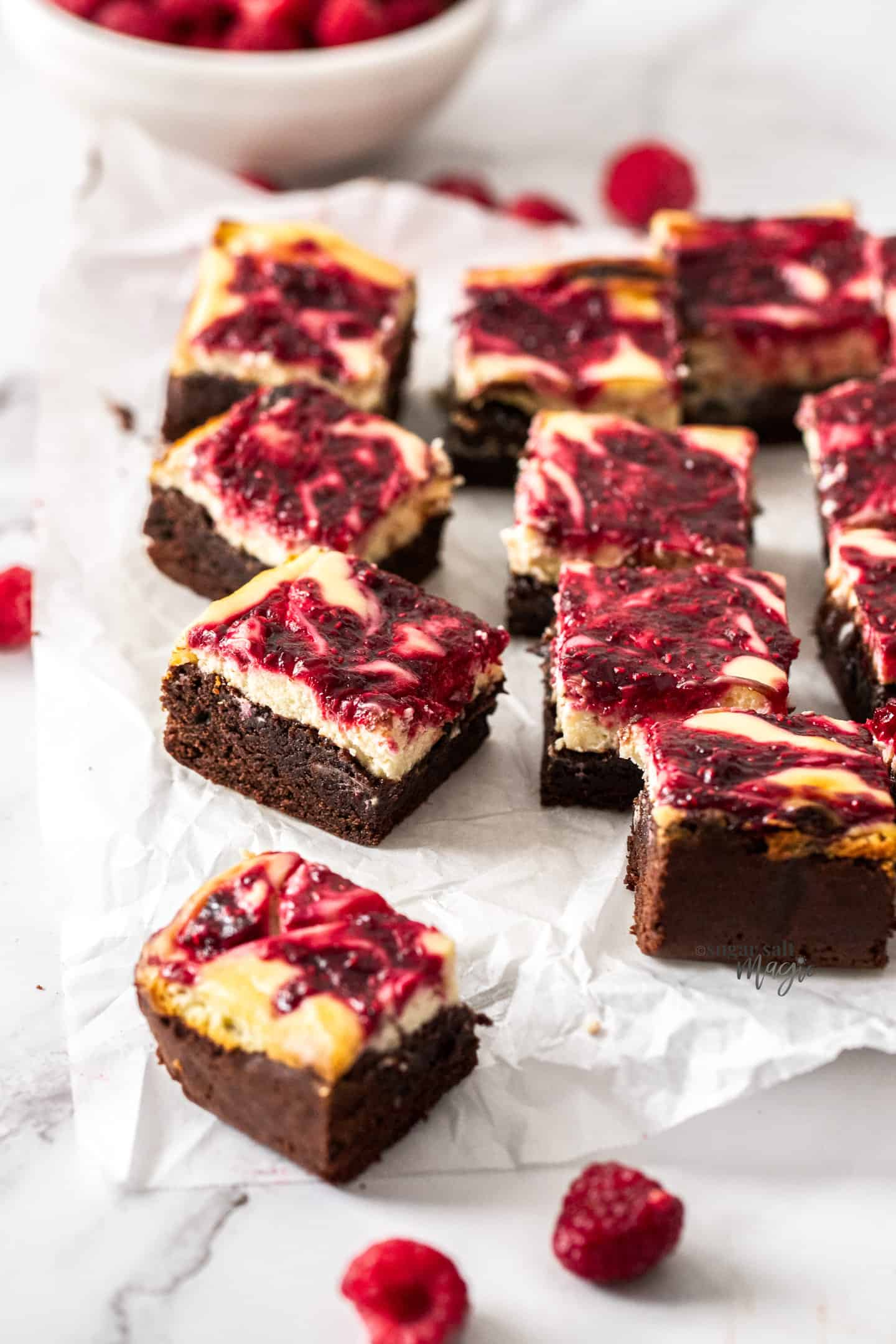 A batch of raspberry cheesecake brownies on a sheet of baking paper.
