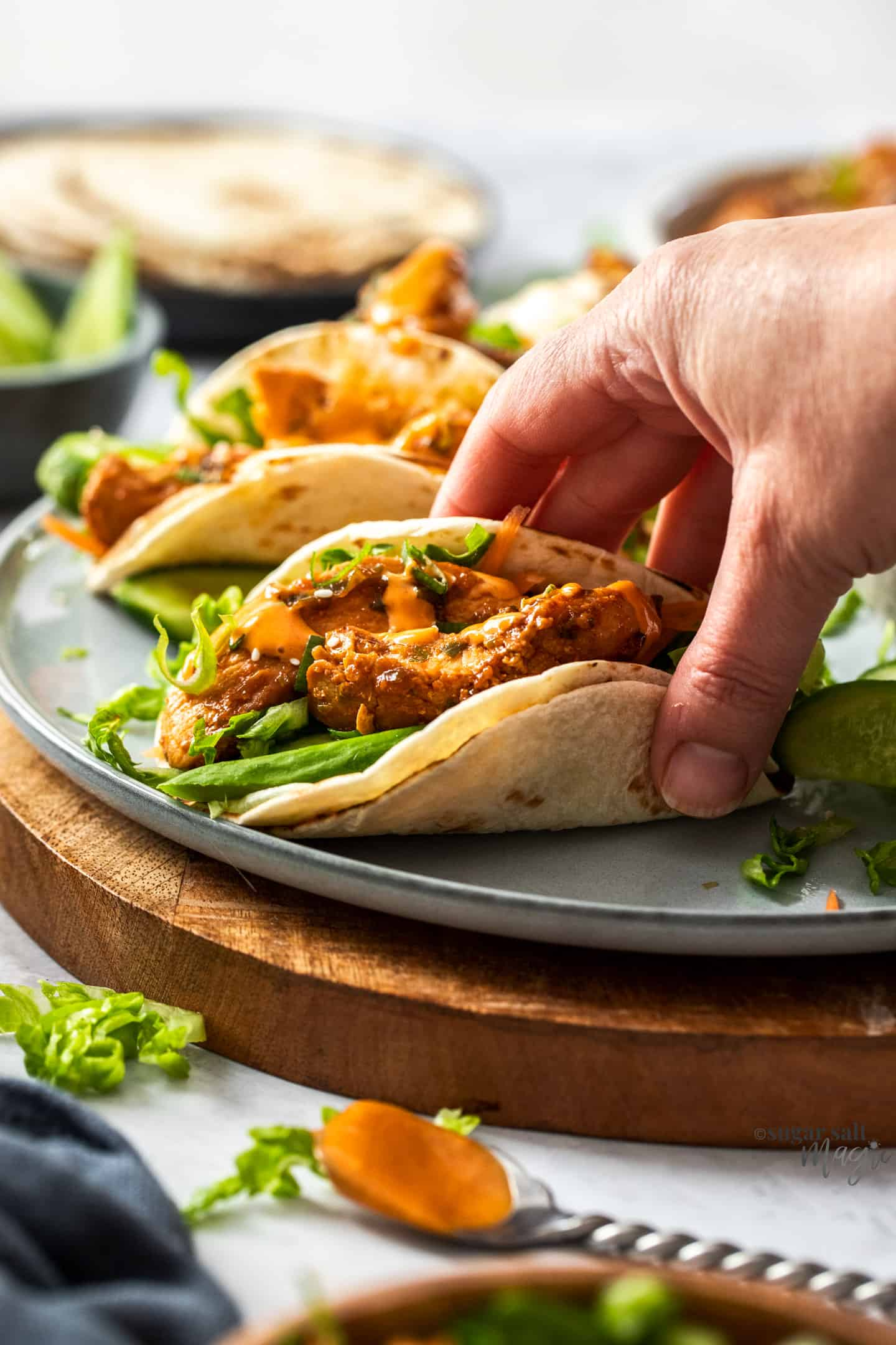 A hand grabbing a taco from a grey plate.