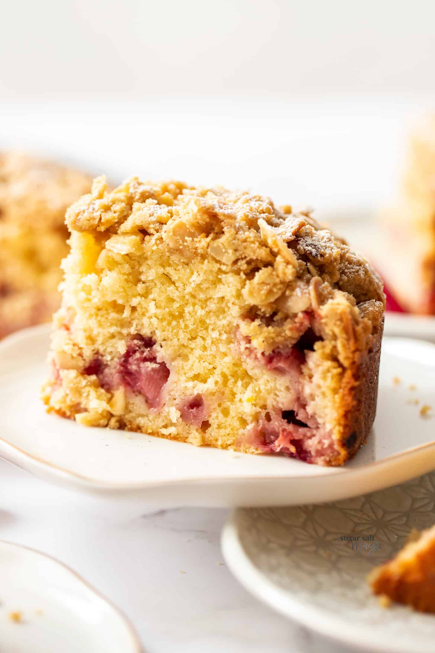 Closeup of a slice of strawberry crumb cake on a white plate.