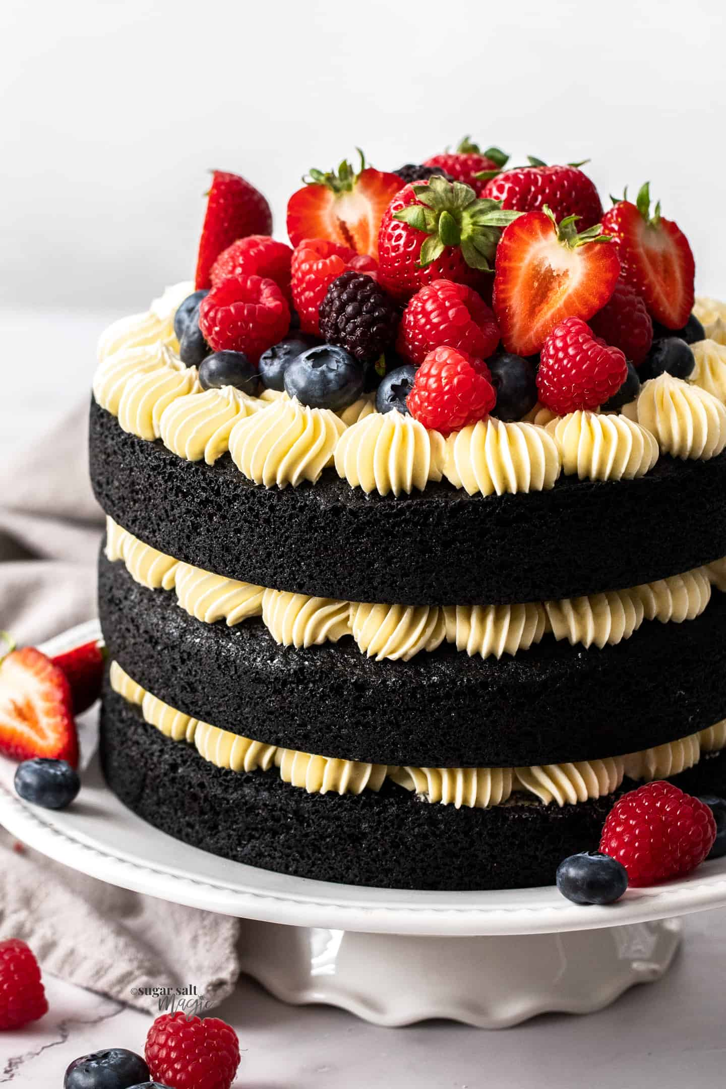 Closeup of a 3 tier black velvet cake with white frosting and berries.