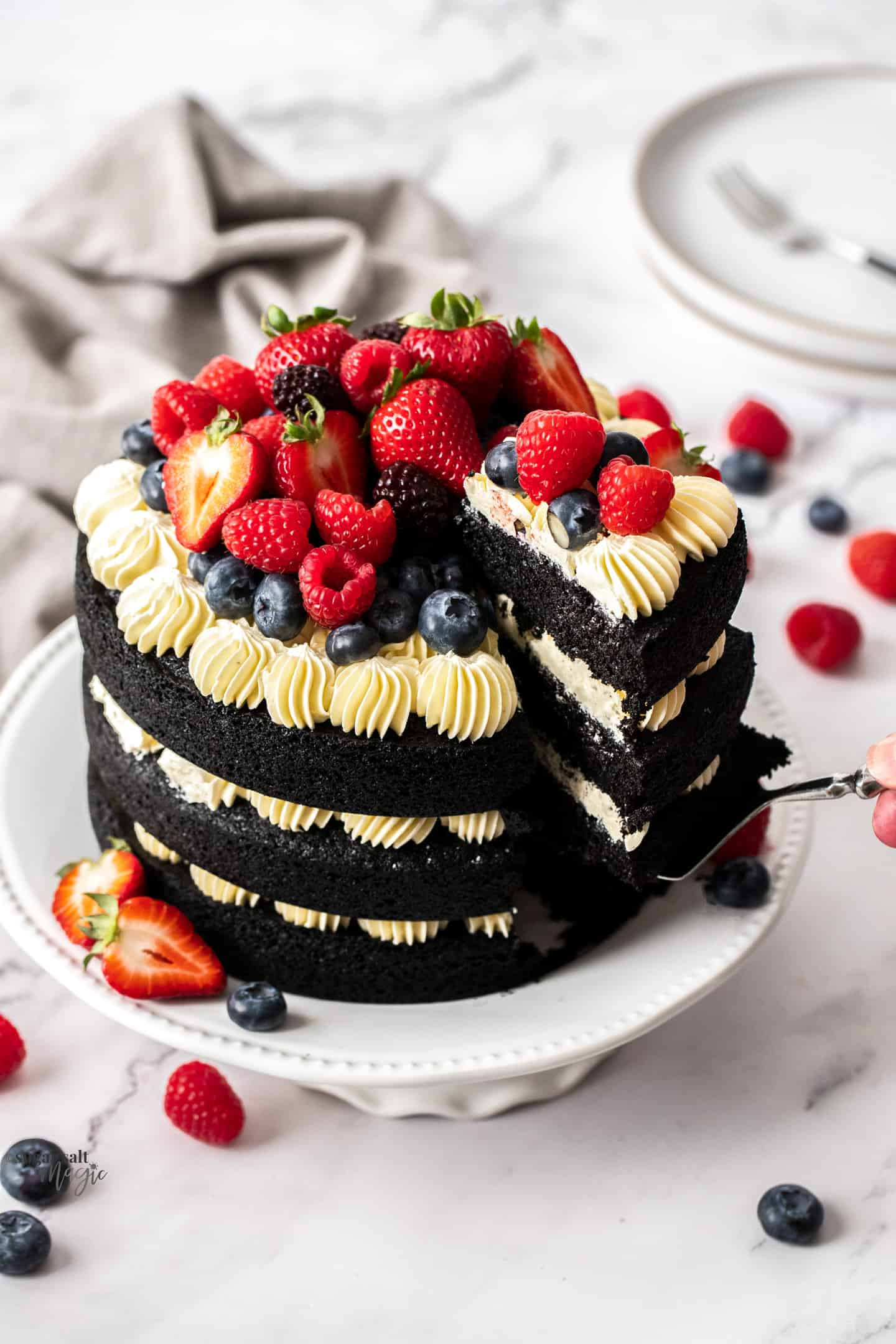 Top down view of a 3 tier black velvet cake topped with fresh berries.