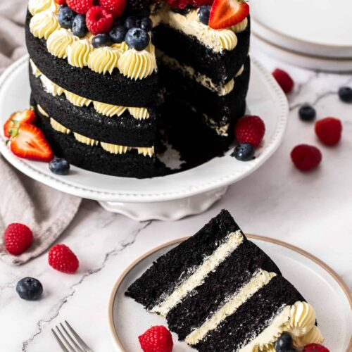 A 3 tier black velvet cake topped with berries, with a slice cut out.