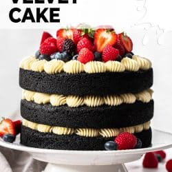 Front on view of a 3 tier black velvet cake topped with fresh berries.