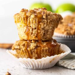 Two stacked muffins with caramel drizzling down the sides.