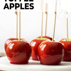 Close up of red toffee apples sitting on a marble platter.
