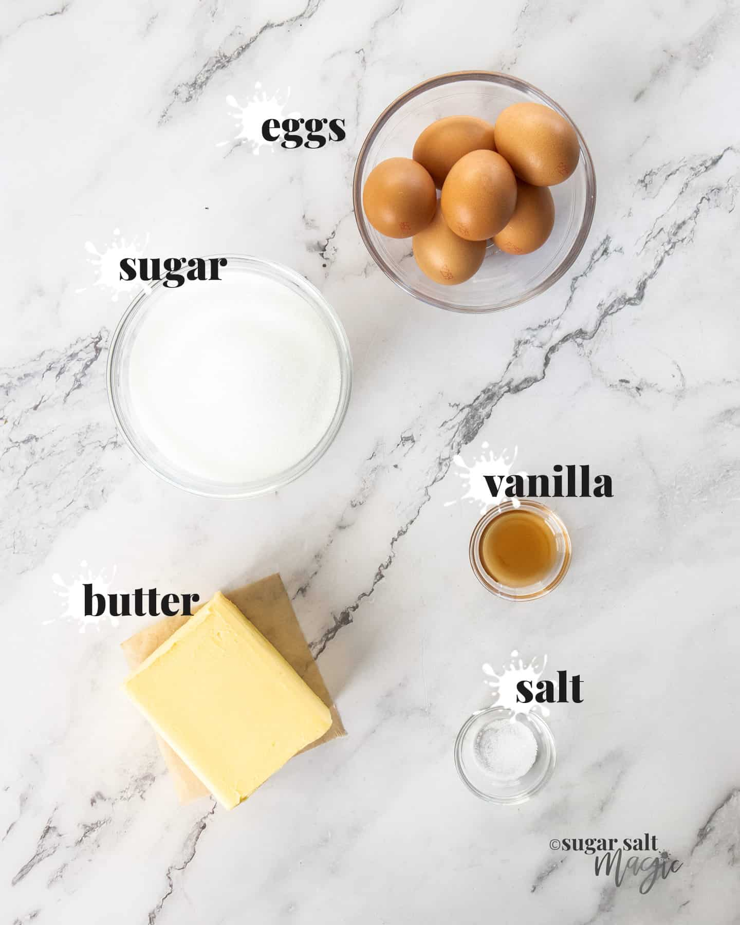 Ingredients for vanilla swiss meringue buttercream on a marble surface.